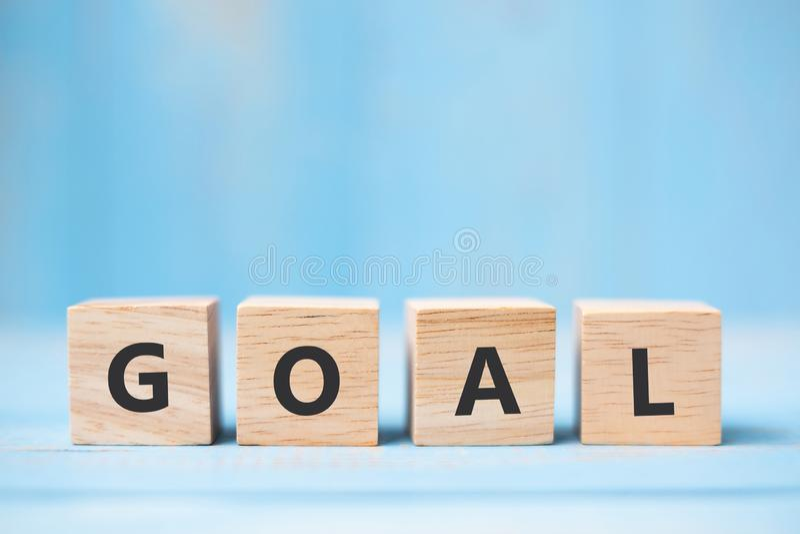 在蓝色桌背景的目标木立方体与文本的拷贝空间 企业、使命、核心价值和解答概念 免版税图库摄影