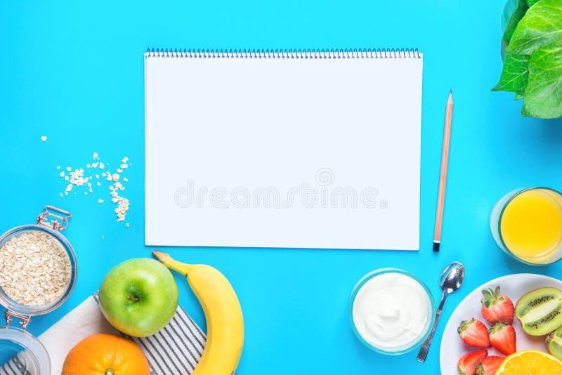 在蓝色桌面的健康早餐燕麦橙汁绿色苹果计算机香蕉草莓猕猴桃酸奶 笔记薄的空白的嘲笑 免版税库存图片