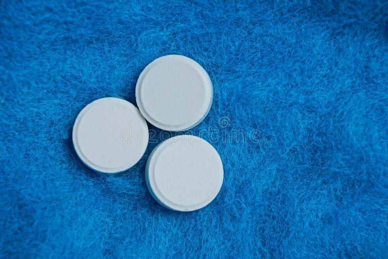在蓝色毛织物品背景的三个白色圆的药片 免版税库存照片