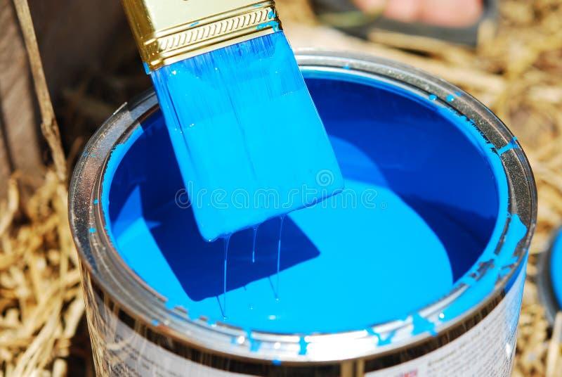 在蓝色油漆的刷子 免版税库存照片