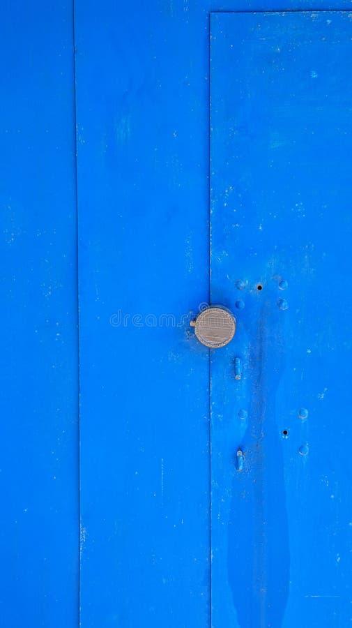 在蓝色油漆盖的一个生锈的金属门的抽象纹理用圆的把柄 免版税图库摄影