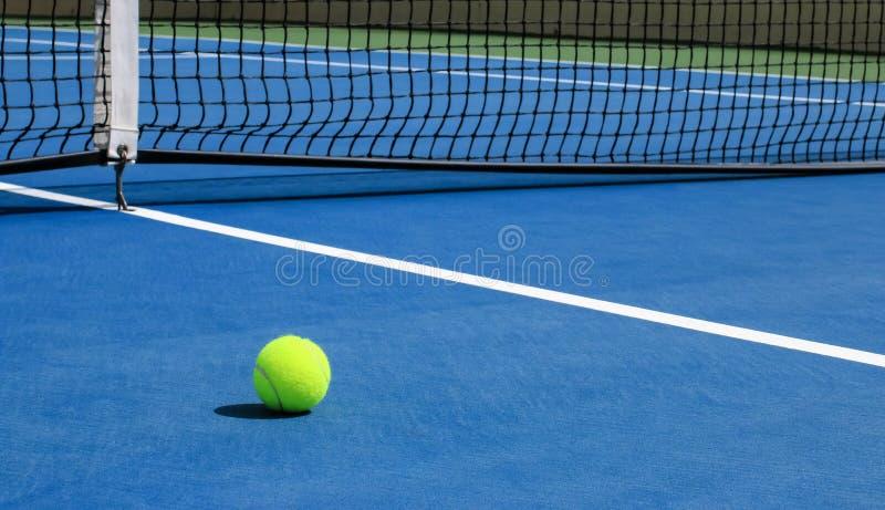 在蓝色法院的网球与网在背景中 库存图片