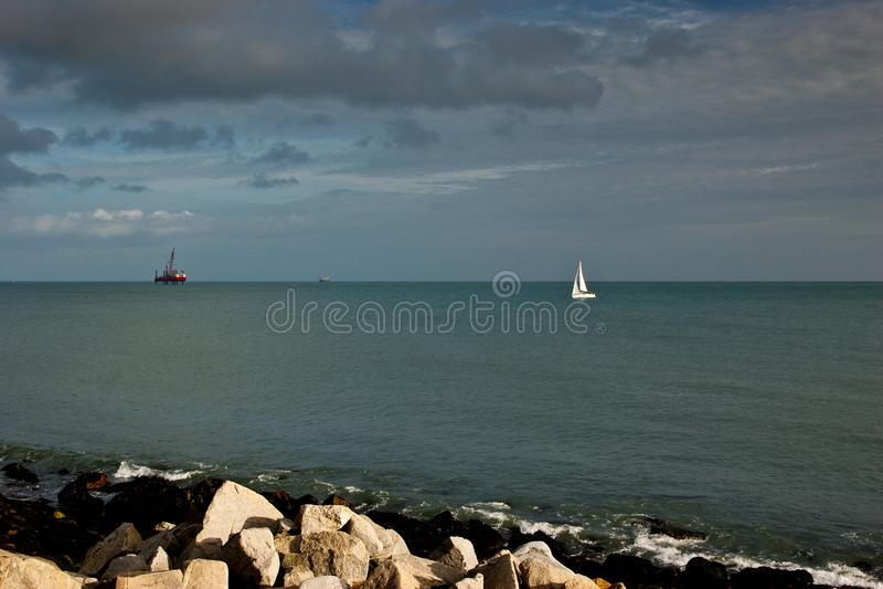 在蓝色海和石油平台,剧烈的天空的小白色风帆游艇航行 免版税库存图片