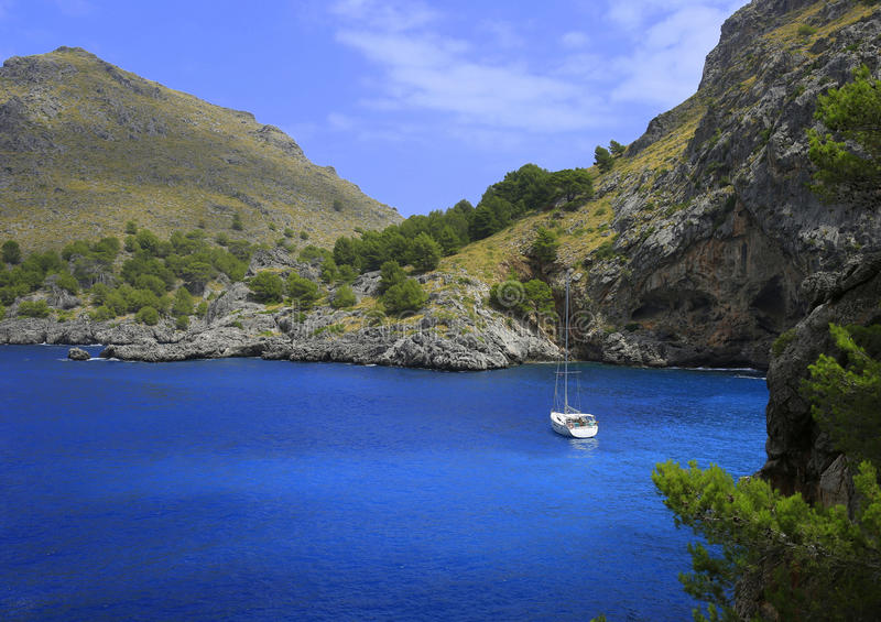 在蓝色海湾的航行游艇和 库存照片