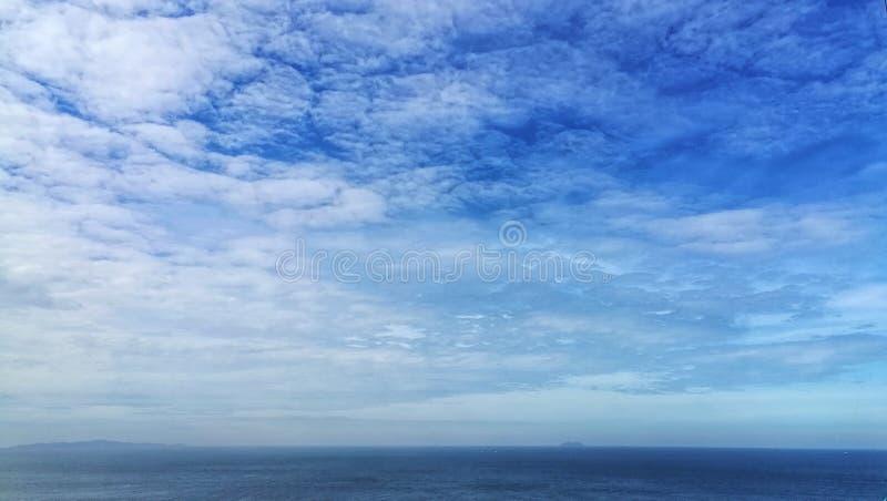 在蓝色海的白色蓬松云彩天空和天际地平线 库存照片