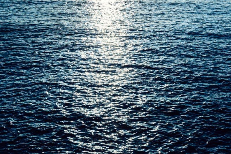 在蓝色海的闪耀的光在日出阳光下挥动水 免版税库存图片