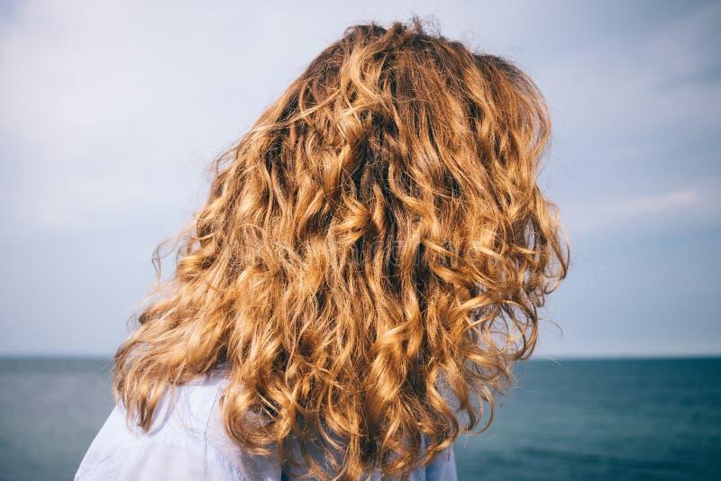 在蓝色海背景的后面看法女性的头 免版税库存图片