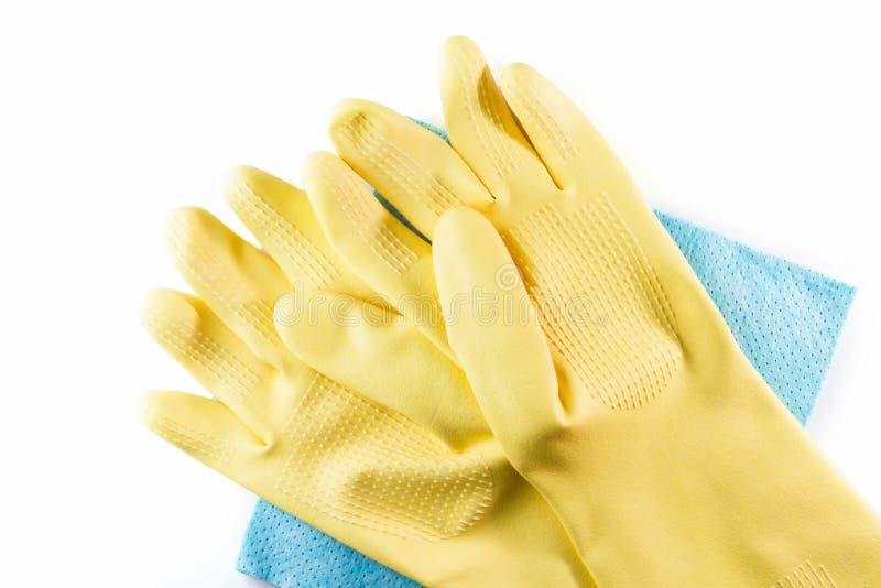 在蓝色清洁餐巾的黄色橡胶手套 库存图片