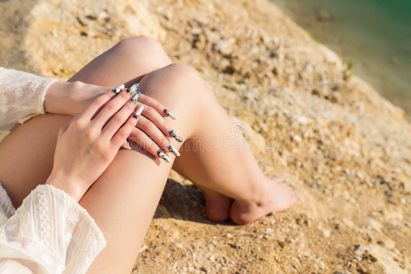在蓝色湖的岸的美好的长的腿,说谎在膝盖的手与长的丙烯酸酯的钉子 免版税库存图片