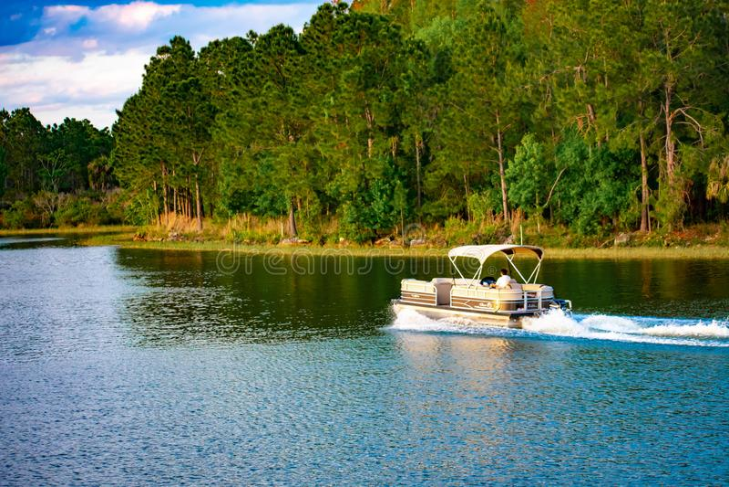 在蓝色湖的海湾小船在华特・迪士尼世界2的绿色森林背景的 库存图片