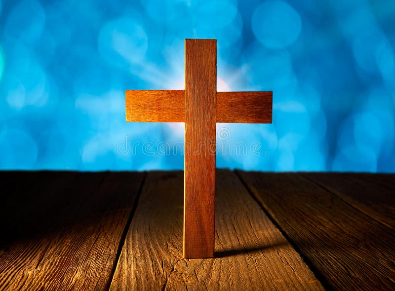 在蓝色火光光的基督徒木十字架 图库摄影