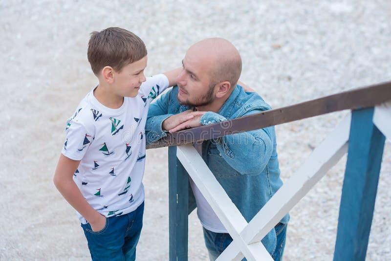 在蓝色焰晕的牛仔裤人穿戴的英俊大胆时髦坐海滩海边与逗人喜爱的儿子男孩青少年的andpretty engli一起 免版税图库摄影