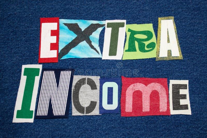 在蓝色牛仔布的额外收入文本词五颜六色的织品拼贴画,旁边忙碌 免版税库存图片