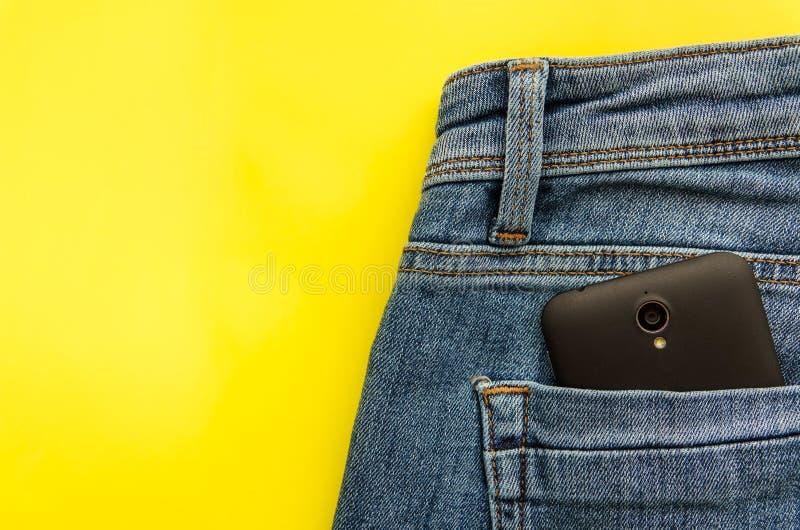 一部分的在蓝色牛仔裤口袋的手机 库存照片