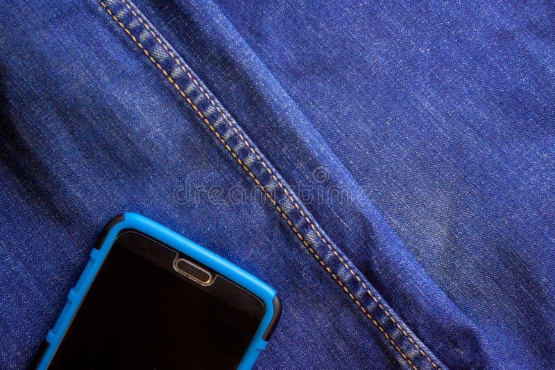 在蓝色牛仔裤外面的一个口袋的智能手机棍子 图库摄影