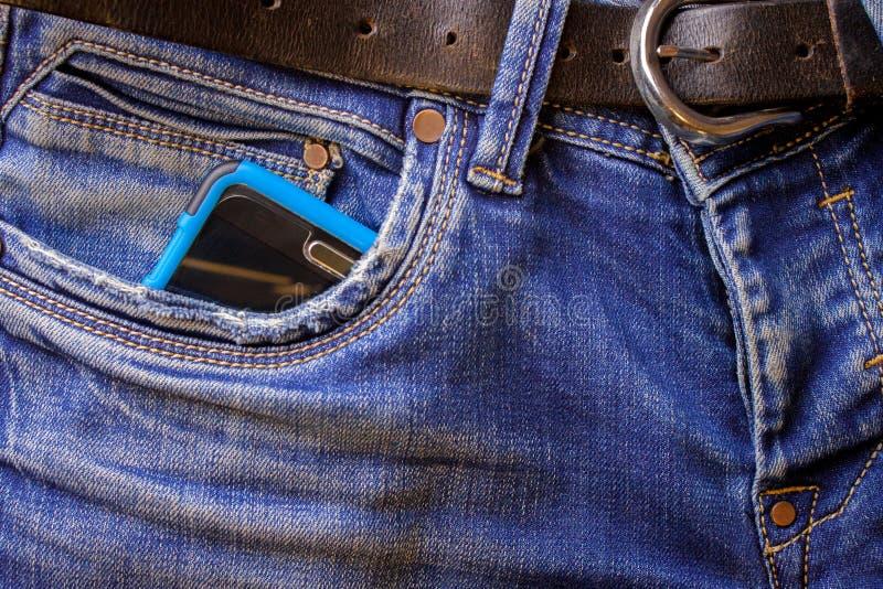 在蓝色牛仔裤外面的一个口袋的智能手机棍子 库存图片