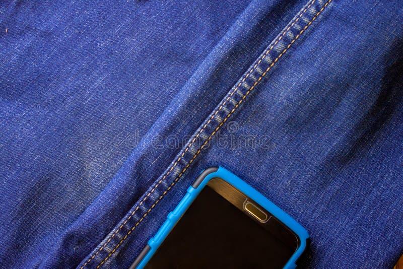 在蓝色牛仔裤外面的一个口袋的智能手机棍子 免版税库存图片