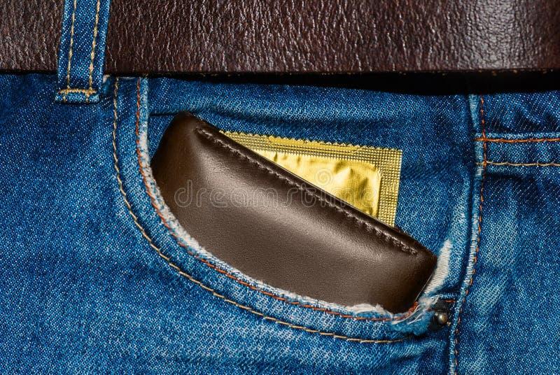 在蓝色牛仔裤的一个口袋的钱包有金避孕套的 图库摄影