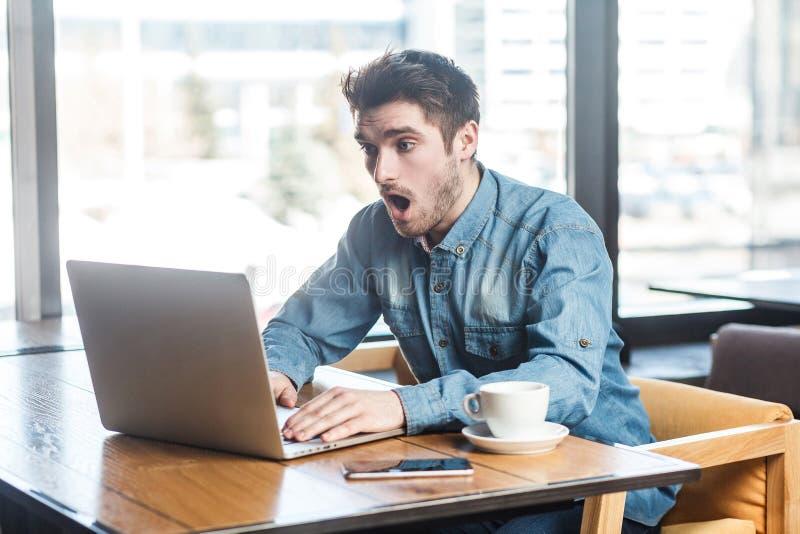 在蓝色牛仔裤衬衣的情感震惊年轻商人在咖啡馆坐,读新闻和远程工作与惊奇的大 免版税库存照片