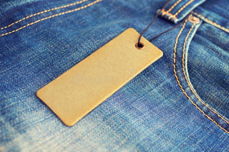 在蓝色牛仔裤的空白的标签价牌大模型 免版税图库摄影