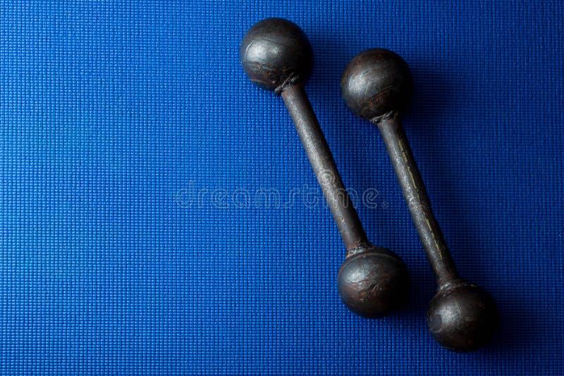 在蓝色瑜伽席子背景的减速火箭的铁难看的东西哑铃 免版税库存照片