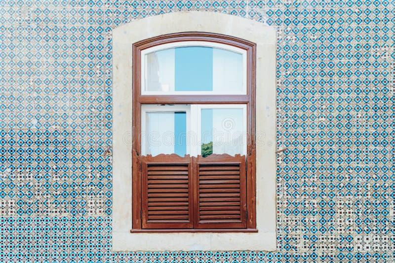 在蓝色瓦片墙壁上的葡萄酒木窗口在里斯本 库存照片