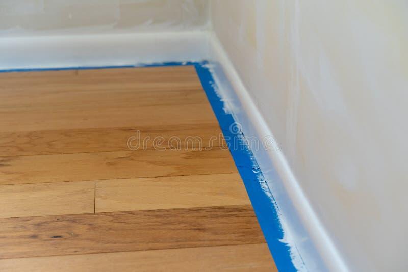 在蓝色画家磁带的部分的选择聚焦在墙壁修剪和硬木地板旁边的,在一张家庭整修和绘画期间 库存照片