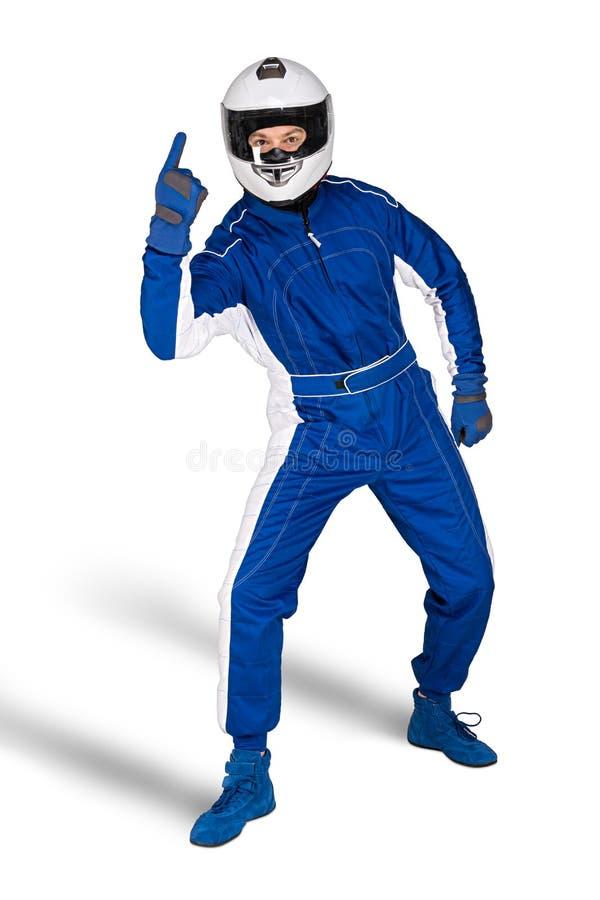 在蓝色白色motorsport整体鞋子手套缺一不可的安全安全帽的坚定的赛车手和白色胜利的手指 免版税库存图片