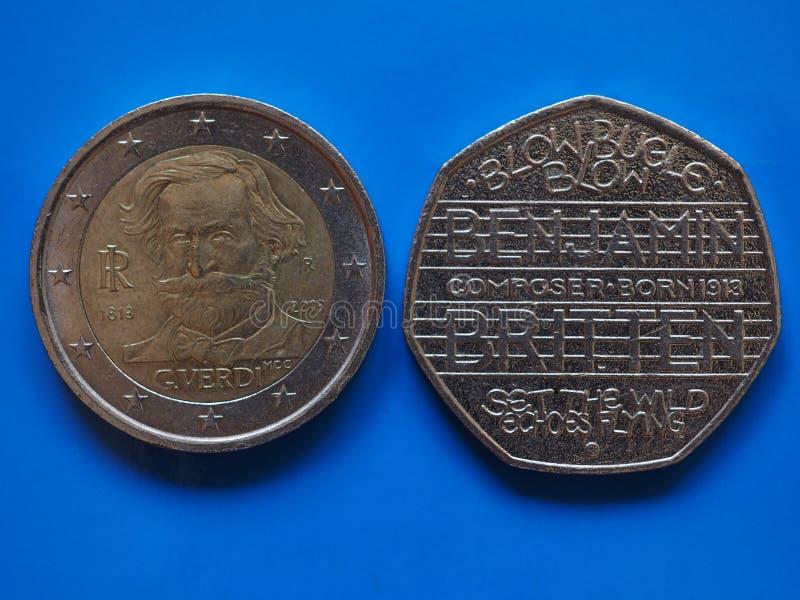 在蓝色的两欧元和20个便士硬币 免版税库存照片