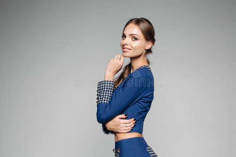 在蓝色的俏丽的模型检查了微笑对照相机的夹克拥抱 库存图片