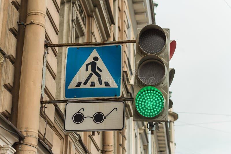 在蓝色的可调整的行人交叉路与瞎的步行者的一枚徽章以黑玻璃的形式 库存照片
