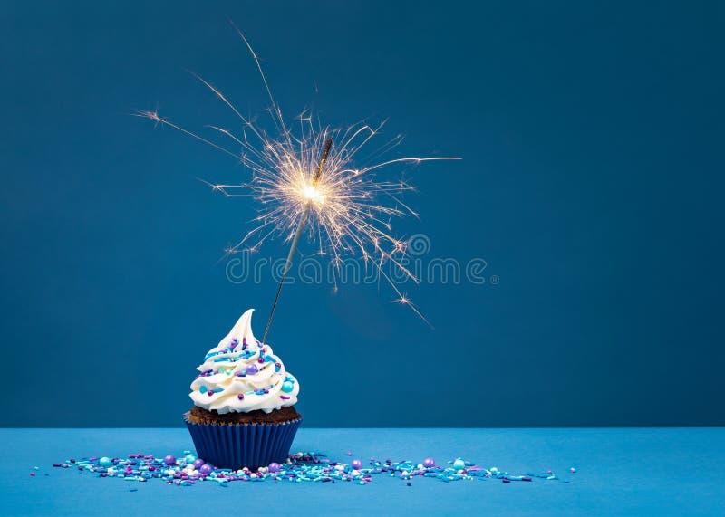 在蓝色的生日杯形蛋糕与闪烁发光物 免版税库存图片