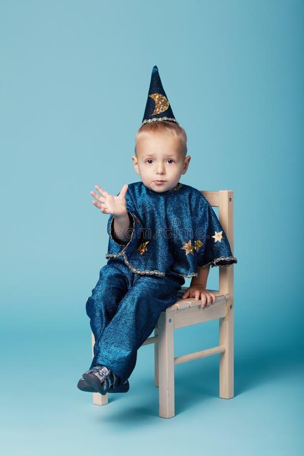 在蓝色的逗人喜爱的小的魔术师画象 免版税库存照片