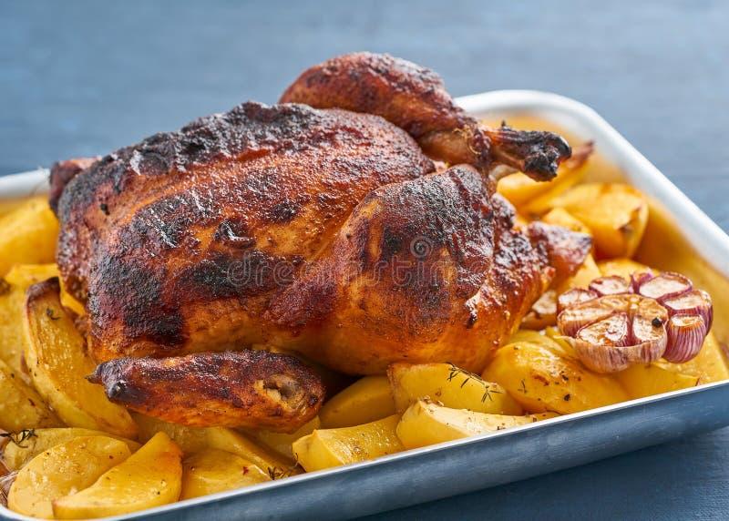 在蓝色砂锅的被烘烤的整鸡在深蓝桌,烤肉上用土豆 o 免版税库存照片