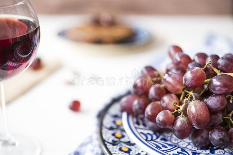 在蓝色碗的束红葡萄,杯红酒,反对迷离背景 免版税库存照片