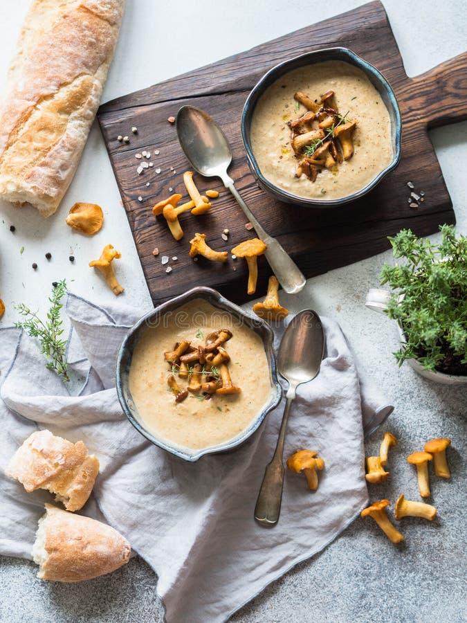 在蓝色碗的黄蘑菇奶油色在土气桌和木头上的汤和长方形宝石上 免版税图库摄影