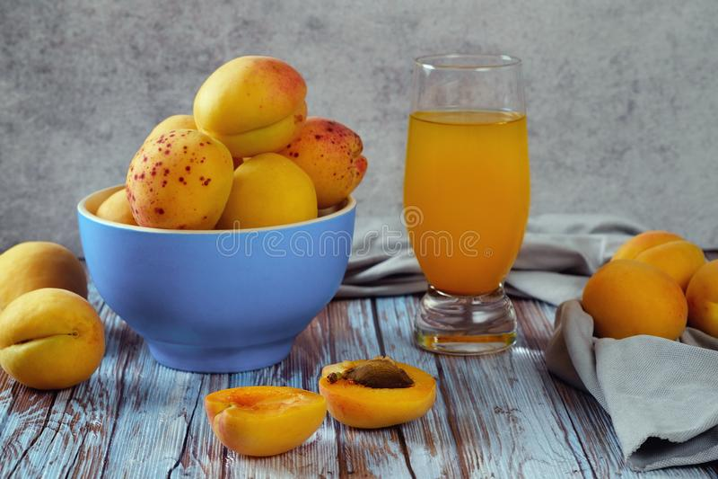在蓝色碗谎言的水多的杏子在轻的木桌和杯上新鲜的杏子汁 免版税库存照片