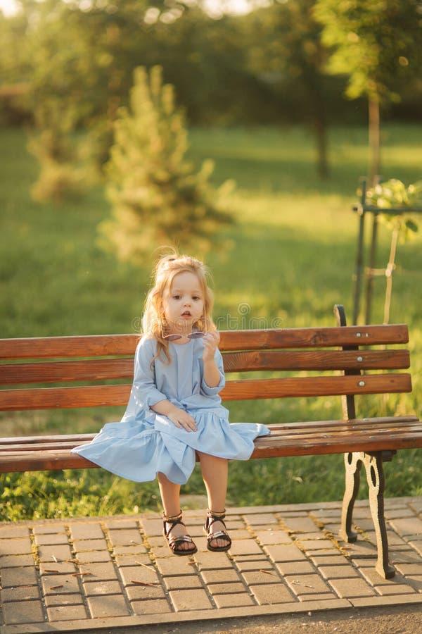 在蓝色礼服和太阳镜的小女孩模型坐一条长凳在公园 免版税库存图片