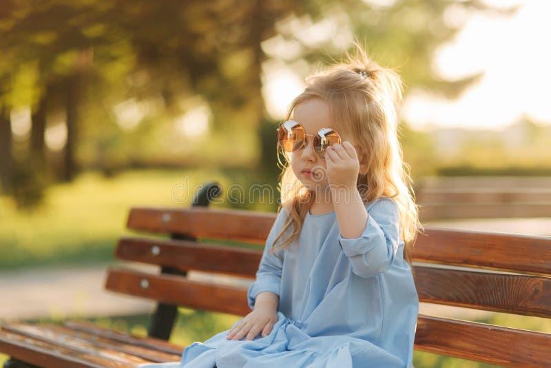 在蓝色礼服和太阳镜的小女孩模型坐一条长凳在公园 免版税库存照片