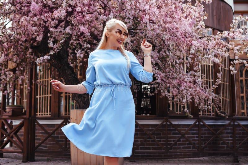 在蓝色礼服的美好的模型在春天开花的树之前 免版税库存照片