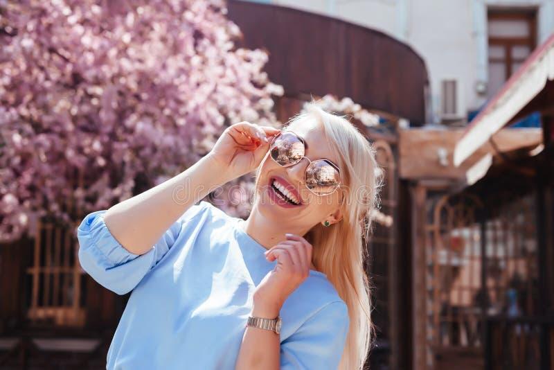 在蓝色礼服的美好的模型在春天开花的树之前 免版税图库摄影