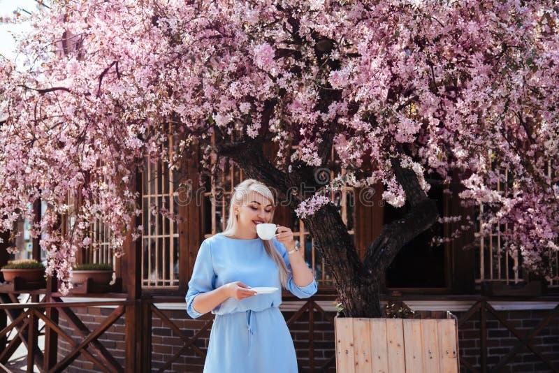 在蓝色礼服的美好的模型在春天开花的树之前 免版税库存图片