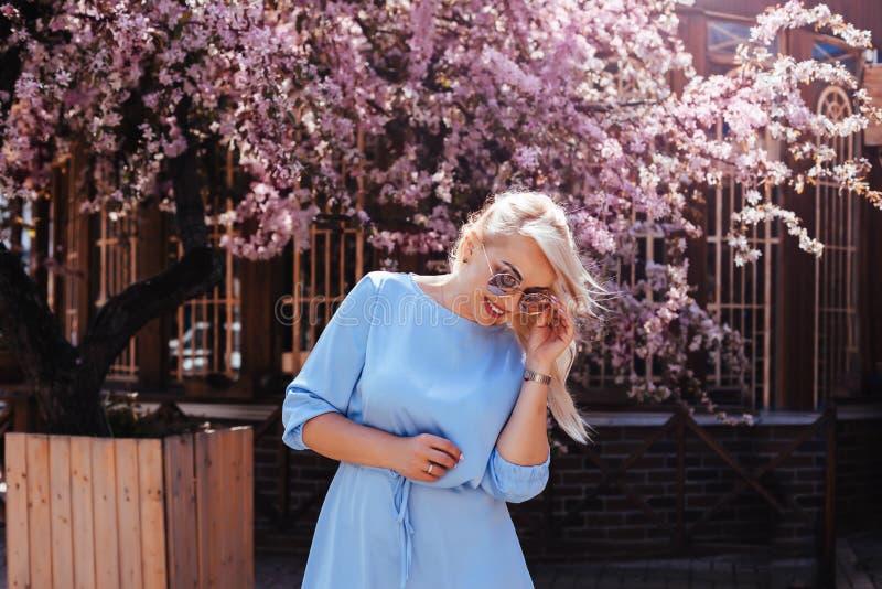 在蓝色礼服的美好的模型在春天开花的树之前 图库摄影