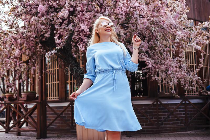 在蓝色礼服的美好的模型在春天开花的树之前 库存照片