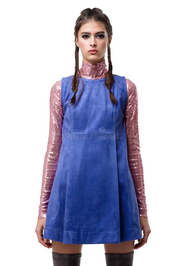 在蓝色绒面革礼服的花姑娘身分和与衣服饰物之小金属片的桃红色上面在被隔绝的白色背景 库存图片