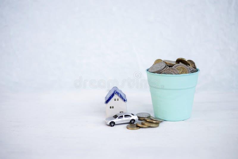 在蓝色罐有微型房子的和汽车的金钱有在白色纹理背景的步幅的 免版税库存图片