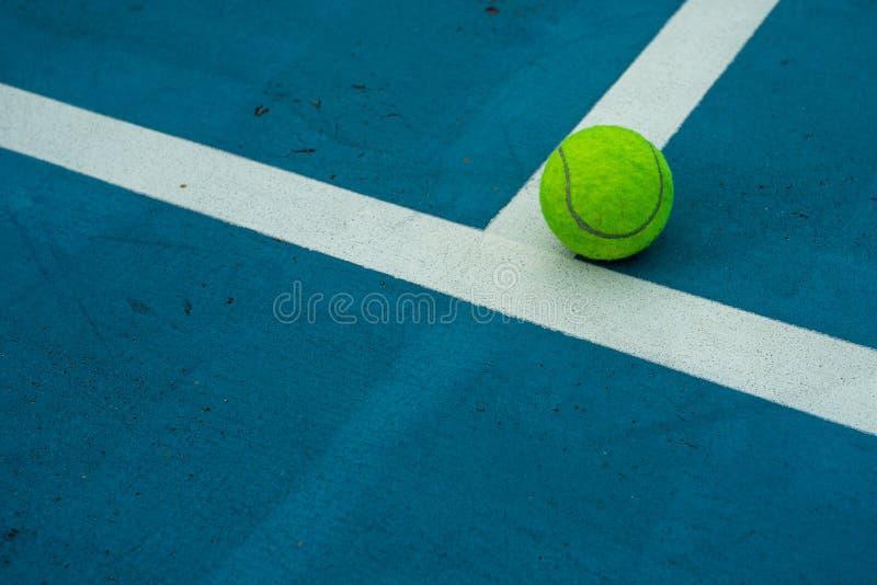 在蓝色网球场的唯一网球 免版税图库摄影