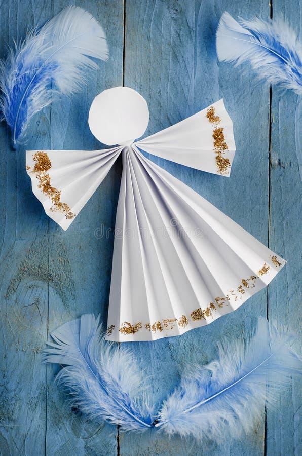 在蓝色羽毛背景的手工纸白色天使 免版税库存照片