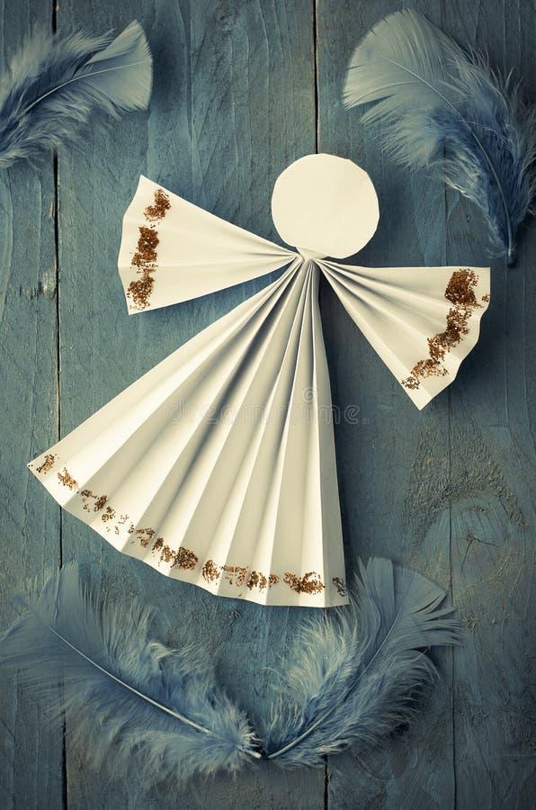 在蓝色羽毛背景的手工纸白色天使 库存照片