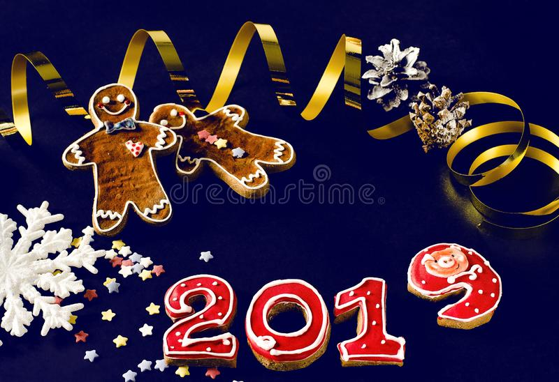 在蓝色背景姜饼红色第2019年与多彩多姿的星的新年卡片姜饼人 免版税库存照片